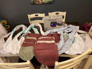 Multiple handmade bat wraps, joey pouches and wallaby bags are laid on a dining room table in front of a sewing machine.