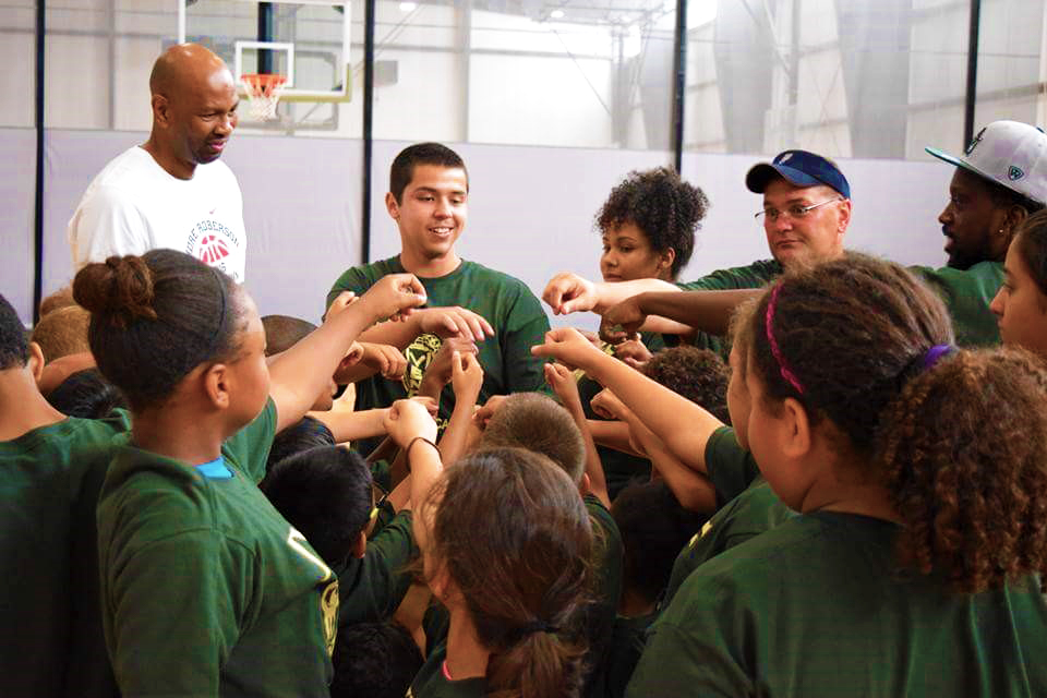 A Terry Scholar stands next to a male coach, leading a team of kids, all placing their hand together in a large circle.