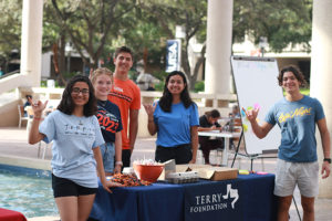 Five Terry Scholars standing around a small information table outdoors