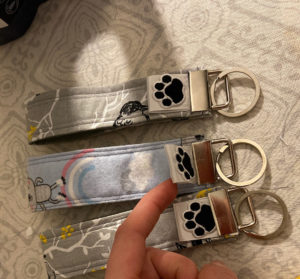 Three small fabric keychains are displayed on a flat surface with a person's finger lifting a small white tag with a dog pawprint.