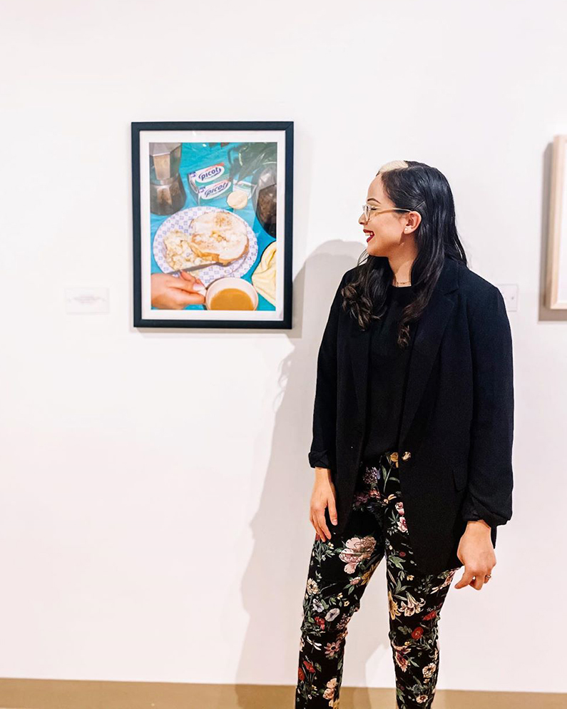 Terry Scholar standing in front of her art work, smiling