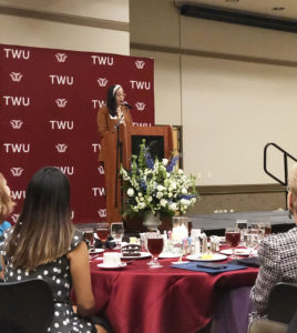 Terry Scholar Olivia Arratia stands at a podium with a TWU maroon backdrop giving a speech at the 2019 TWU Terry Scholars Banquet