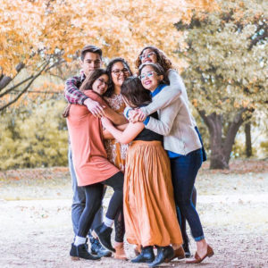 Terry Scholar, Olivia Arratia, with her 5 siblings outdoors. All are hugging and smiling.